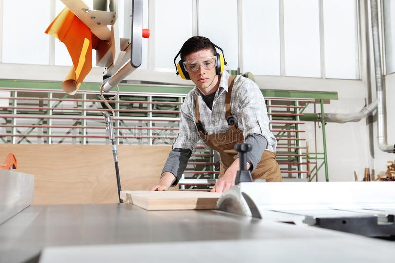 Carpenter man work in the joinery, cut a wooden board with circular saw machine, protected with ear muffs. And glasses stock photography