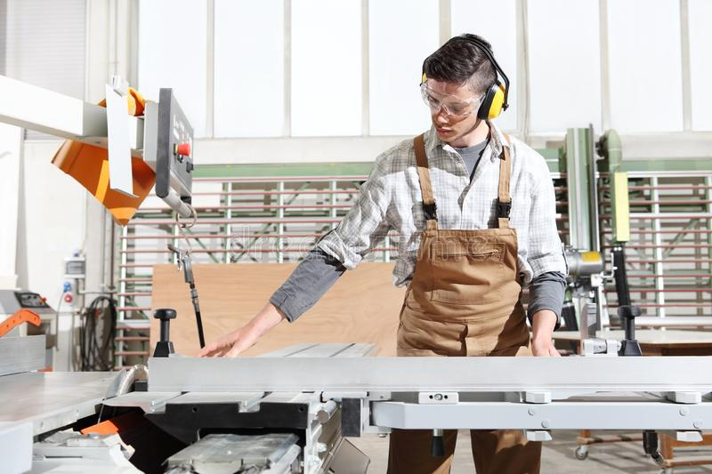 Carpenter man work in the joinery, cut a wooden board with circular saw machine, protected with ear muffs. And glasses royalty free stock photos