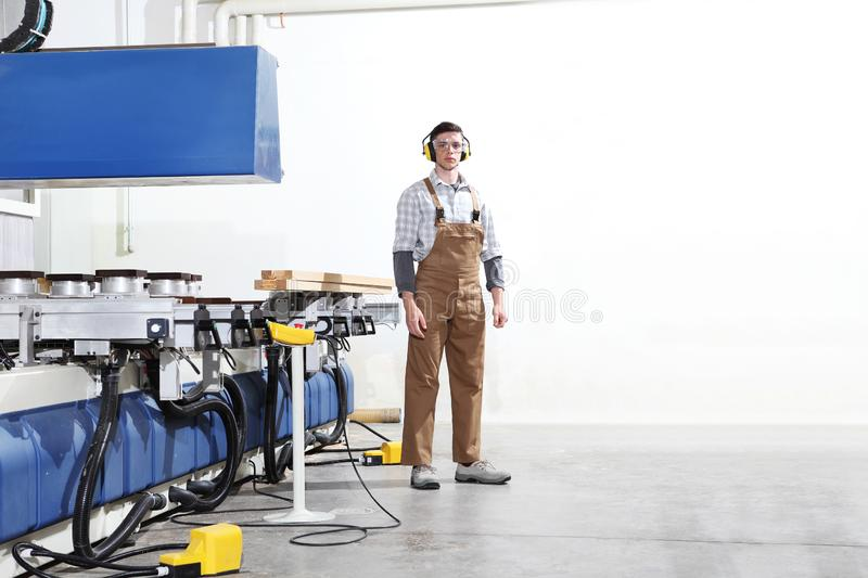 Carpenter man works with wooden planks in the joinery, with computer numerical control center, cnc machine,  isolated on a white. Background royalty free stock image