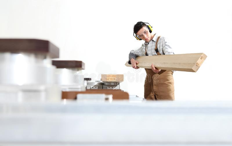 Carpenter man works with wooden planks in the joinery, with computer numerical control center, cnc machine,  isolated on a white. Background stock photography