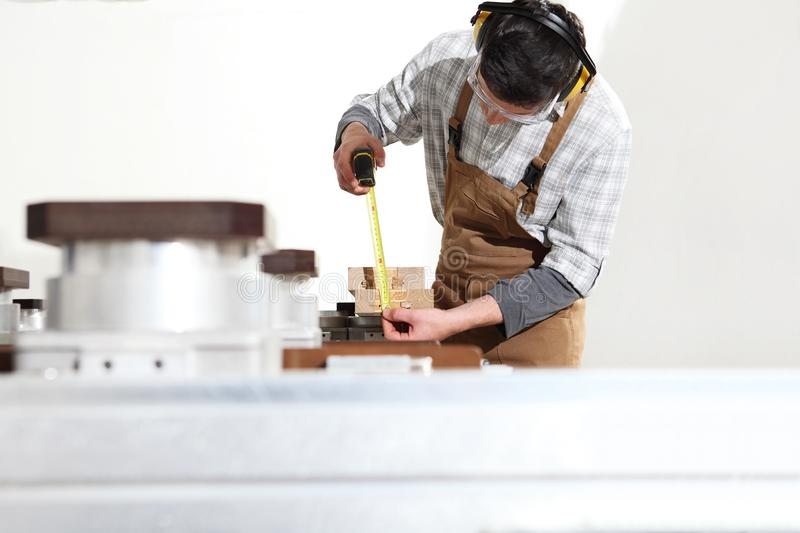 Carpenter man works with wooden planks in the joinery, measure with meter, with computer numerical control center, cnc machine, stock photography