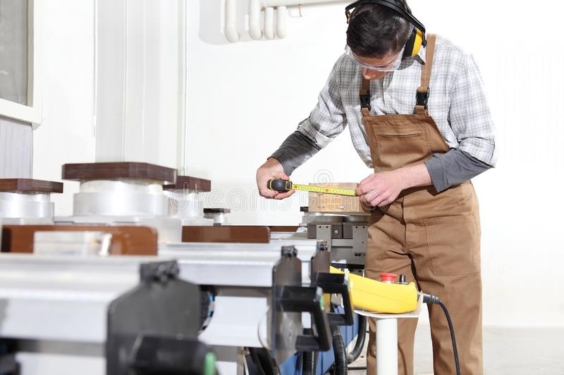 Carpenter man works with wooden planks in the joinery, measure with meter, with computer numerical control center, cnc machine, stock image