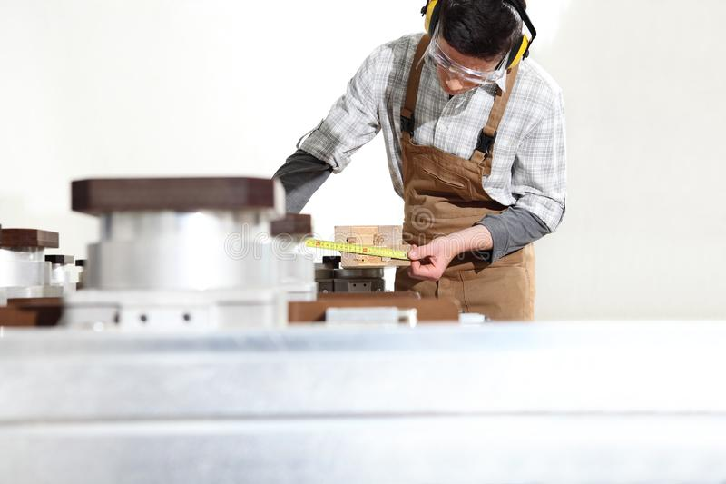 Carpenter man works with wooden planks in the joinery, measure with meter, with computer numerical control center, cnc machine, stock photos