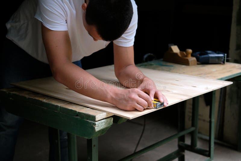 Carpenter marking straight line on plywood sheet using spirit level in carpentry workshop. Measuring, drawing line, DIY concept royalty free stock image