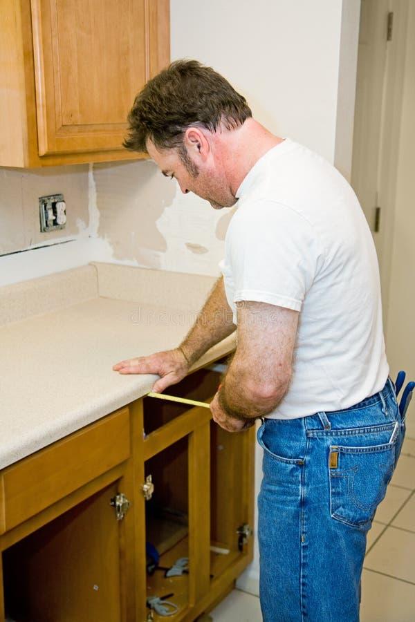 Download Carpenter Measuring Cabinets Royalty Free Stock Image - Image: 6883536