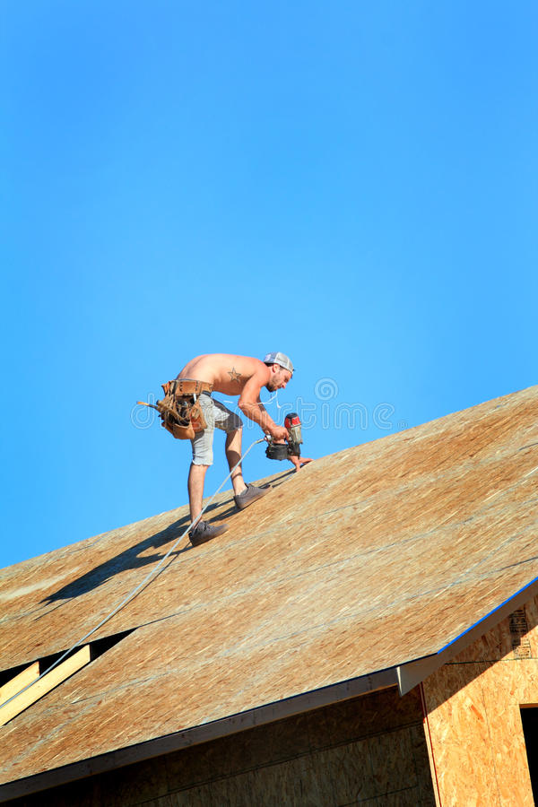 Carpenter with Nail Gun. A carpenter working on a roof with a nail gun on top of a house that is under construction royalty free stock photos