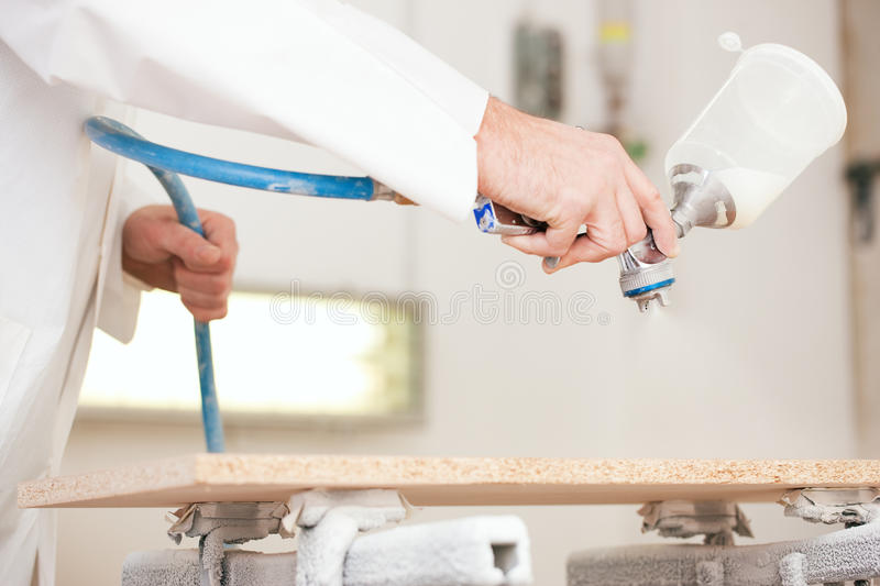Carpenter painting wood with airbrush stock image