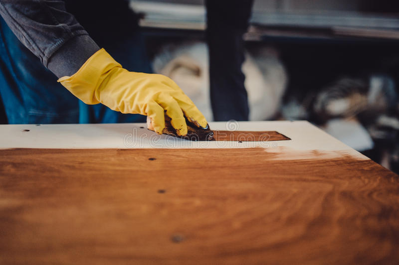 Carpenter is painting a wood with lacquer stock image