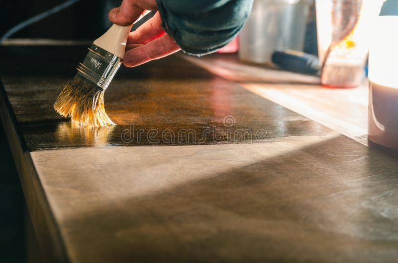 Carpenter covers wood furniture parts with wood wax. Carpenter paints tinted wood furniture details with wax for wood brush, close-up stock photography