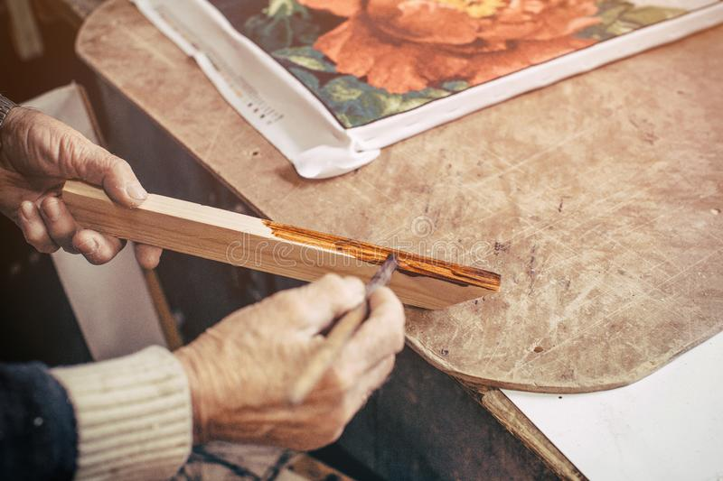 The carpenter paints a wooden blank to make a frame in his baguette workshop. stock images