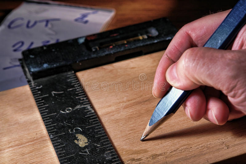 Carpenter Pencil and Square in Wood Worker Hand stock image