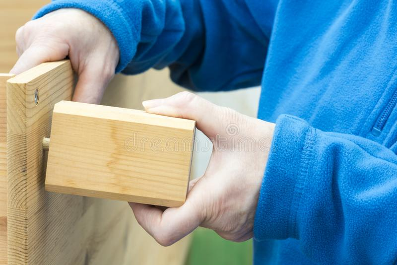 Carpenter places the leg of the furniture. Carpenter places the foot of a piece of furniture royalty free stock photo
