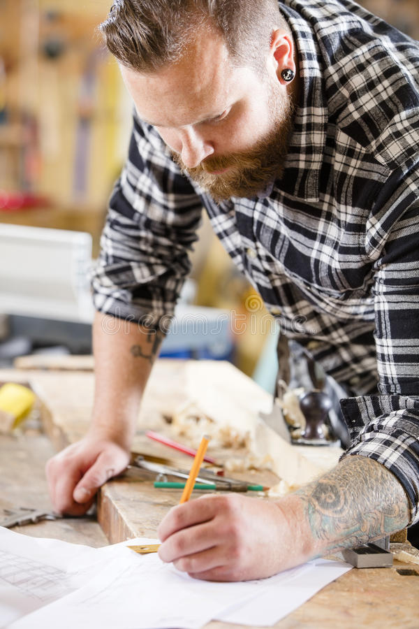 Carpenter plans work and notes at project drawings royalty free stock photos