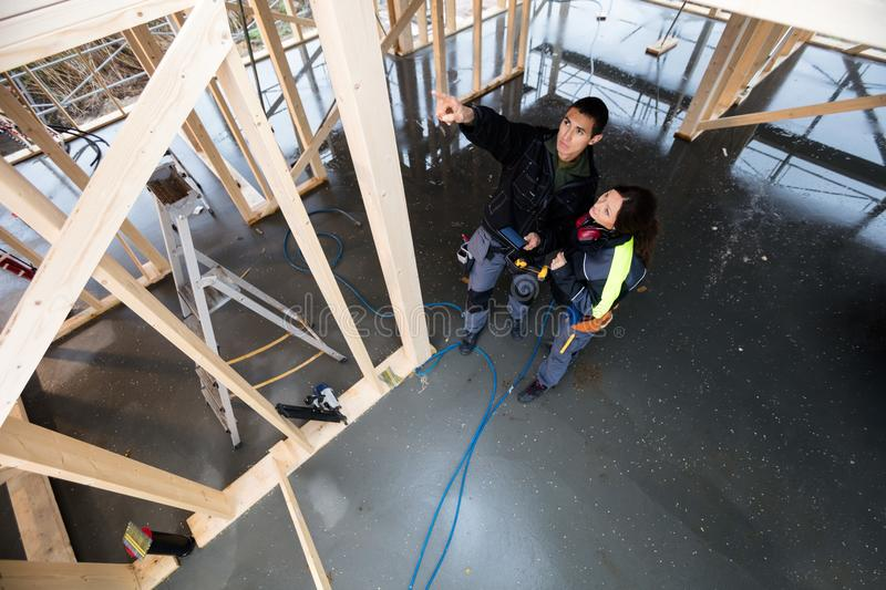 Carpenter Pointing By Female Colleague In Incomplete Architectur. High angle view of young male carpenter pointing while standing by female colleague in royalty free stock photos
