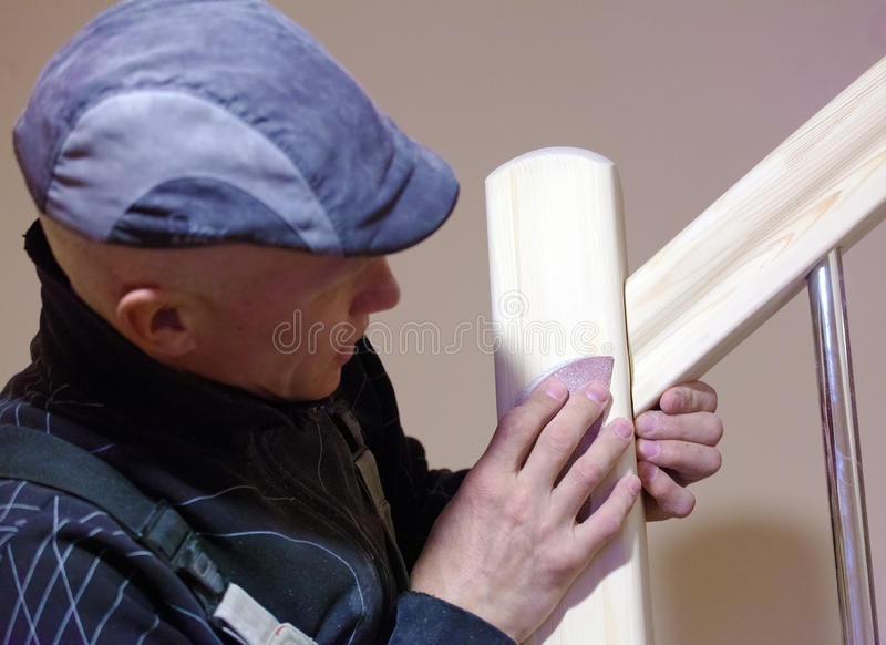 Carpenter Polishing Modern Ladder with Sandpaper stock image