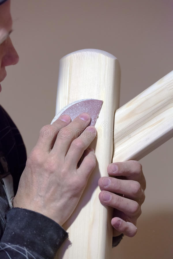 Carpenter Polishing Modern Ladder with Sandpaper stock photography