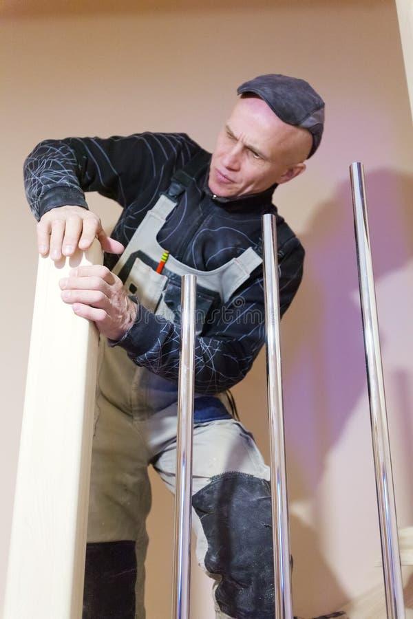 Carpenter Polishing Modern Ladder with Sandpaper royalty free stock image