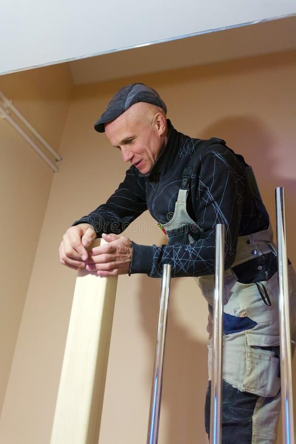 Carpenter Polishing Modern Ladder with Sandpaper stock photo