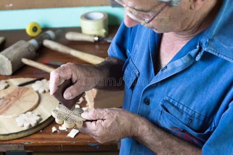 Carpenter polishing a wooden figure royalty free stock photos