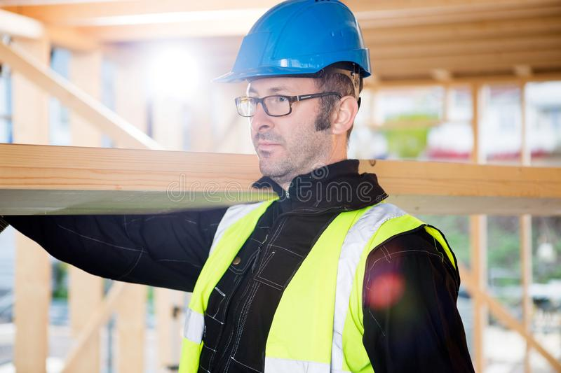 Carpenter In Protective Wear Carrying Wood On Shoulder. Male carpenter in protective wear carrying wood on shoulder at construction site royalty free stock photography