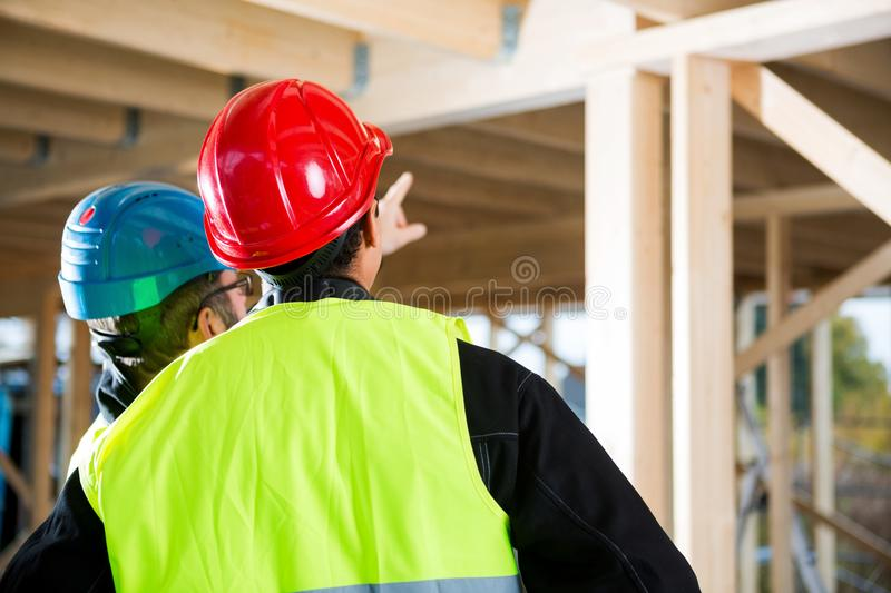 Carpenter In Protective Wear Standing By Colleague. Rear view of carpenter in protective wear standing by colleague at construction site stock photography