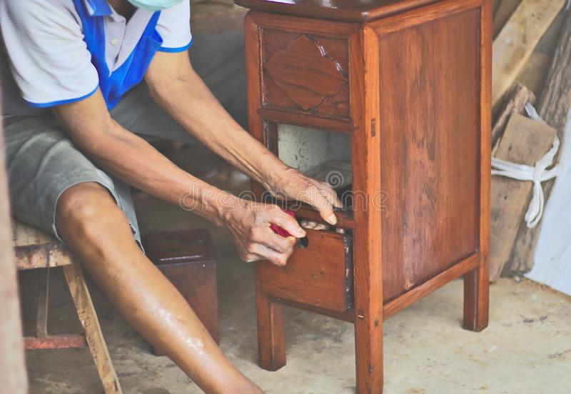 Carpenter repairing wooden drawers Three floors, small, new furniture, red wood, old Thai, polished, background color, people. Working with hands, conserving royalty free stock photography