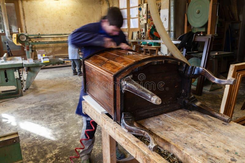 Carpenter restoring Wooden Furniture in his workshop stock photos