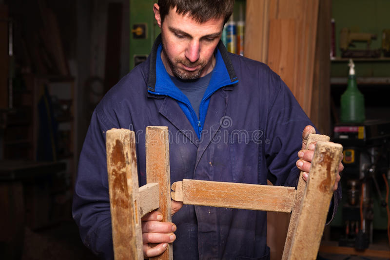 Carpenter restoring Wooden Stool Furniture in his workshop. royalty free stock photo