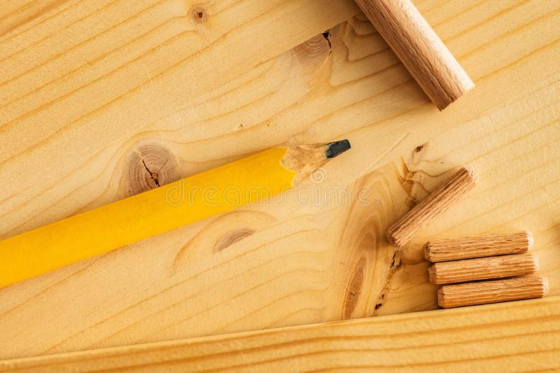 Carpenter`s pencil and wooden dowels on work desk. Top view stock photos