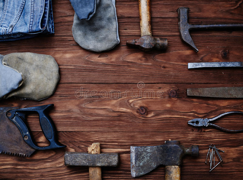 Carpenter's working hand tools forming a frame. Working hand tools carpenter forming a frame isolated on grunge wooden background royalty free stock photos