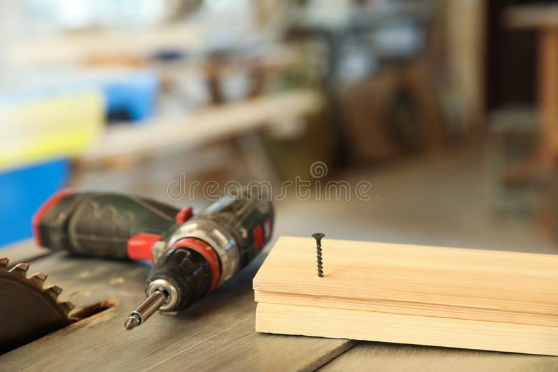 Carpenter`s working place with electric screwdriver and timber strip on table. Indoors royalty free stock photo