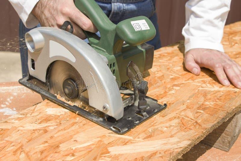 Carpenter`s workshop. Carpenter cuts the OSB stock photography