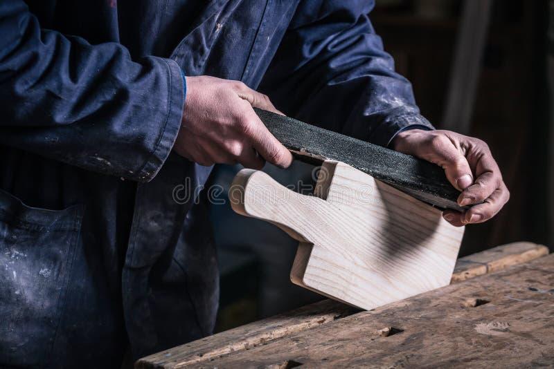 Carpenter sanding piece of Timber with sandpaper stock photos