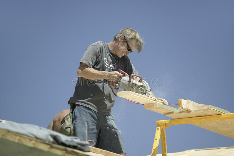 Download Carpenter Sawing Board On Roof Editorial Stock Photo - Image: 27071223