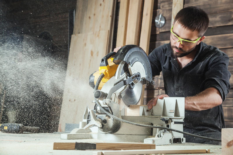 Carpenter saws a circular saw. Close-up as a young male construction worker carpenter saws a circular saw blade, sawdust fly in the workshop stock images