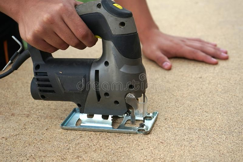 Carpenter saws wood slab with a jigsaw royalty free stock photos