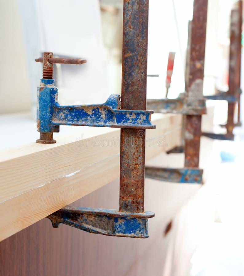 Carpenter clamp tool pressing wood slats stock photos