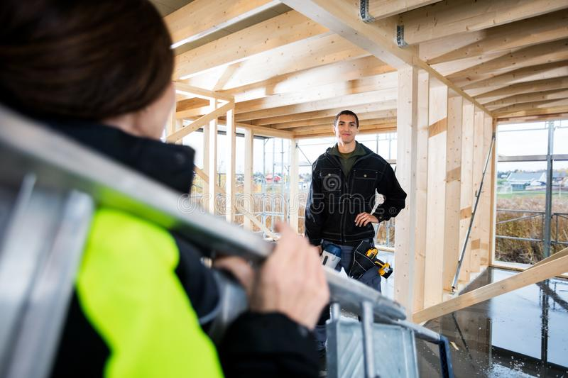 Carpenter Standing While Colleague Carrying Ladder In Incomplete. Portrait of male carpenter standing while female colleague carrying ladder in incomplete royalty free stock images