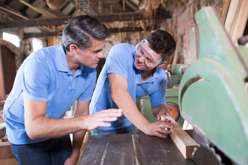 Carpenter Teaching Apprentice How To Use Circular Saw stock images