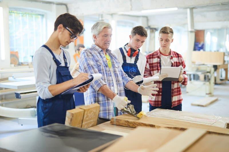 Carpenter teaching students to polish wooden planks stock image