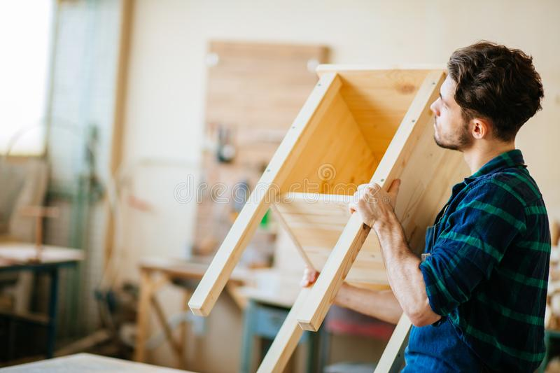 Carpenter testing wood plank evenness at workshop royalty free stock photography
