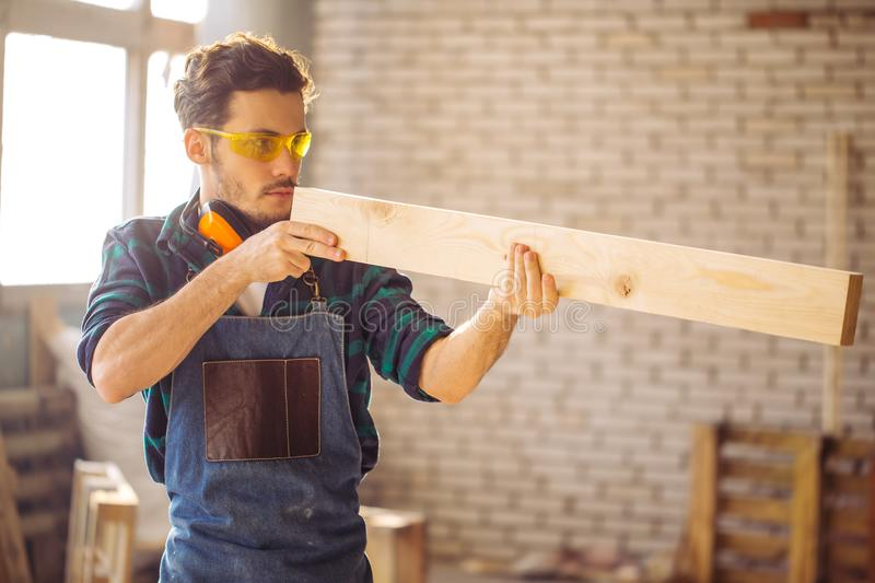 Carpenter testing wood plank evenness at workshop royalty free stock image