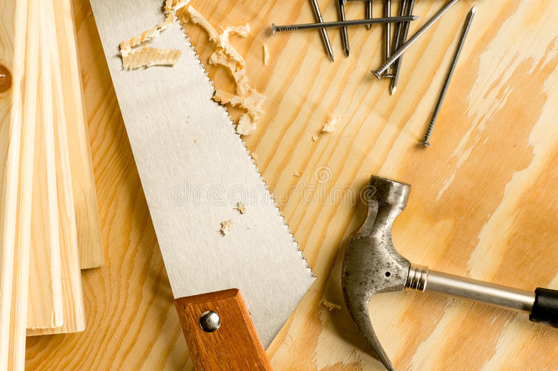Carpenter tools. Carpenter wood saw, roofing hammer, nails and slats stock photography