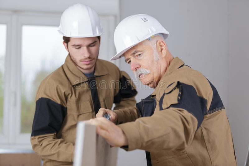 Carpenter trainee learning with boss. Apprentice royalty free stock photo