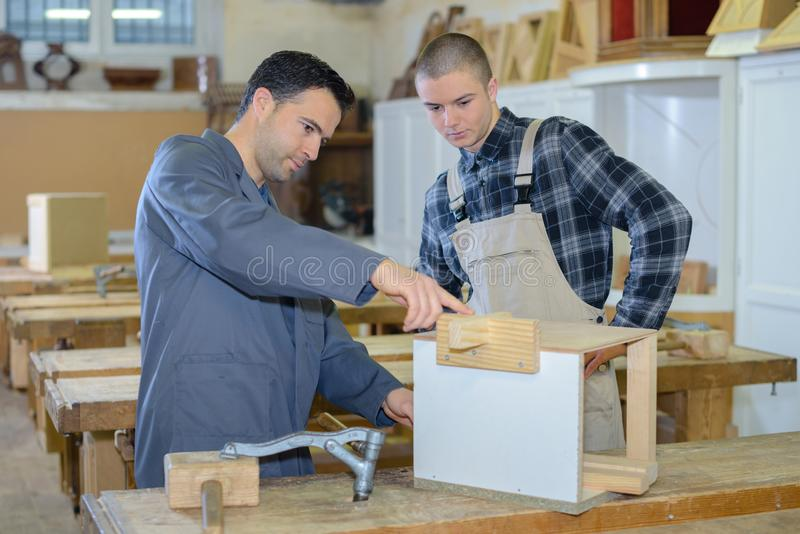 Carpenter trainee listening to teacher in workshop stock photography