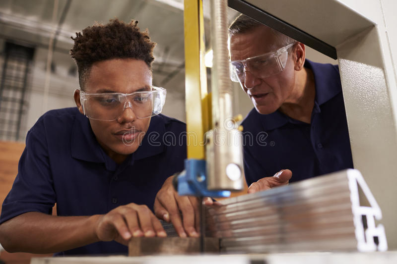 Carpenter Training Male Apprentice To Use Mechanized Saw royalty free stock photos