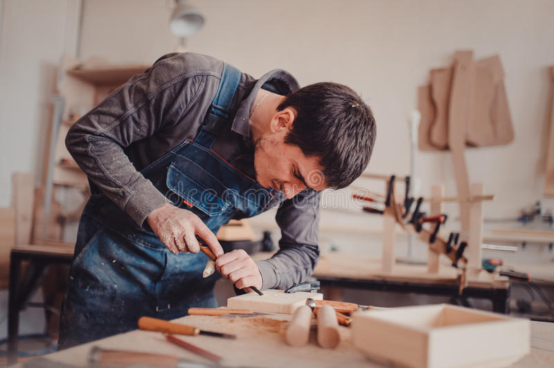 Carpenter use a chisel to shapes a wooden plank. royalty free stock image