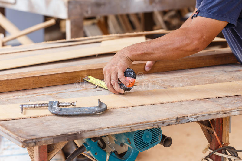 Carpenter use saw cut wood for make new furniture. Photo carpenter use saw cut wood for make new furniture royalty free stock images