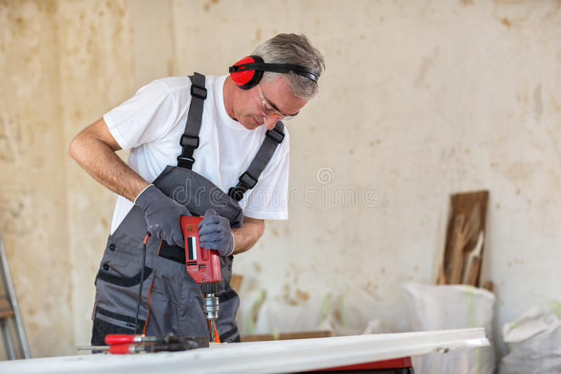 Carpenter used drills in reparation of old doors stock photo