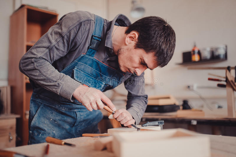 Carpenter use a chisel to shapes a wooden plank. royalty free stock photography